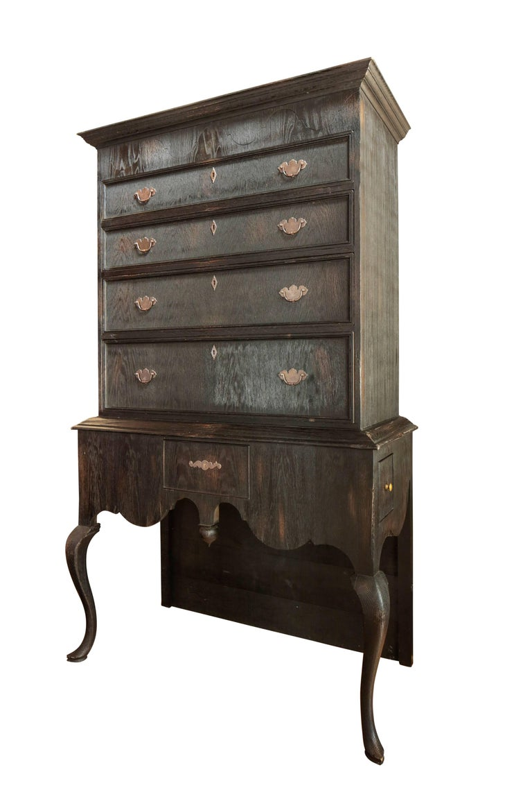 The 'Great Scott' highboy in ebonized oak. The upper section with a molded rectangular and hinged top opens along the frieze to reveal a hidden compartment. The conforming case with four drawers rests atop the lower section with three small drawers