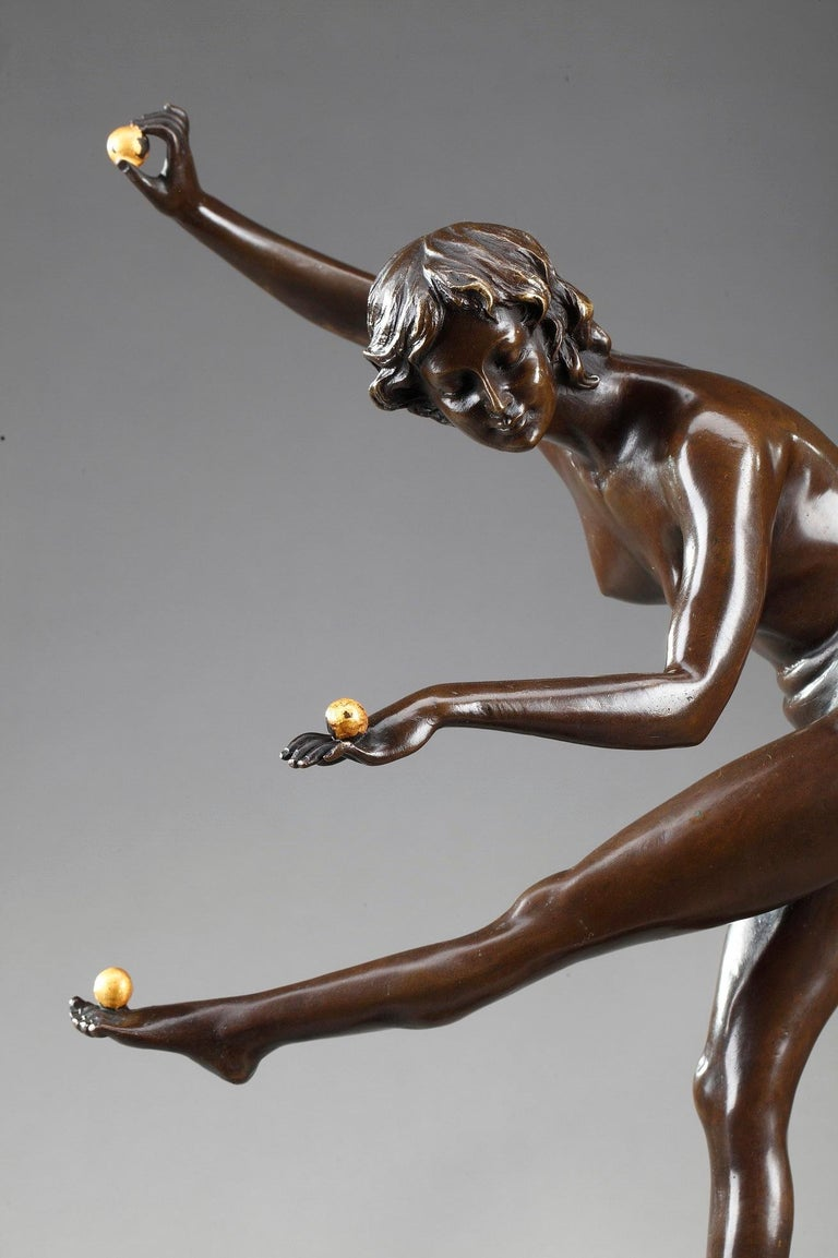 Bronze sculpture with brown patina featuring a young woman juggling three gilded balls, on a small circular base. The base is chiseled with foliage and small pearls. The bronze is set upon a black marble plinth. Signed Cl. JR COLINET and Bronze