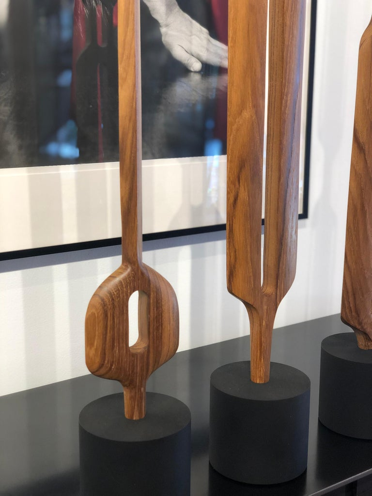 Teak is a dense tropical hardwood with a gray to brown color and finely textured with a tight grain and smooth surface when polished. These hand carved and shaped totem sculptures bring out the natural beauty of the wood's graceful structure. Each