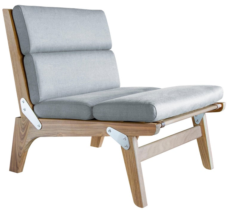 The O.F.S. folding lounge chair in unfinished teak and link outdoor - weathered or sterling fabric with faux leather straps. This chair is available in non-folding and folding versions (shown). This chair is also available as an indoor chair.  Our
