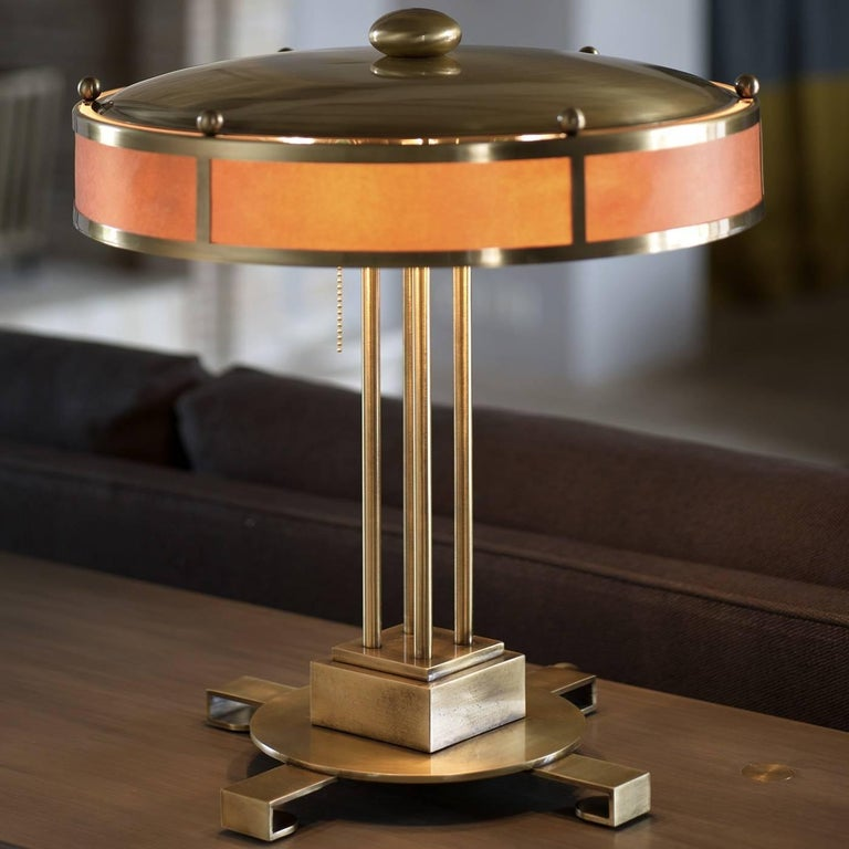 The splendour of the Italian design of the early 1930s has been reinterpreted in a modern way with this stylish table lamp. Entirely crafted of brass-plated steel, with a circular base supported by four L-shaped feet, a structure made of a square