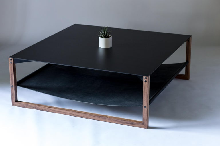 The Sling, modern aluminum, leather and walnut square coffee table.  Minimal and elegant form paired with a balanced and thoughtful design. The Sling coffee table features powder-coated aluminum, blackened hand-stitched leather, and hand finished