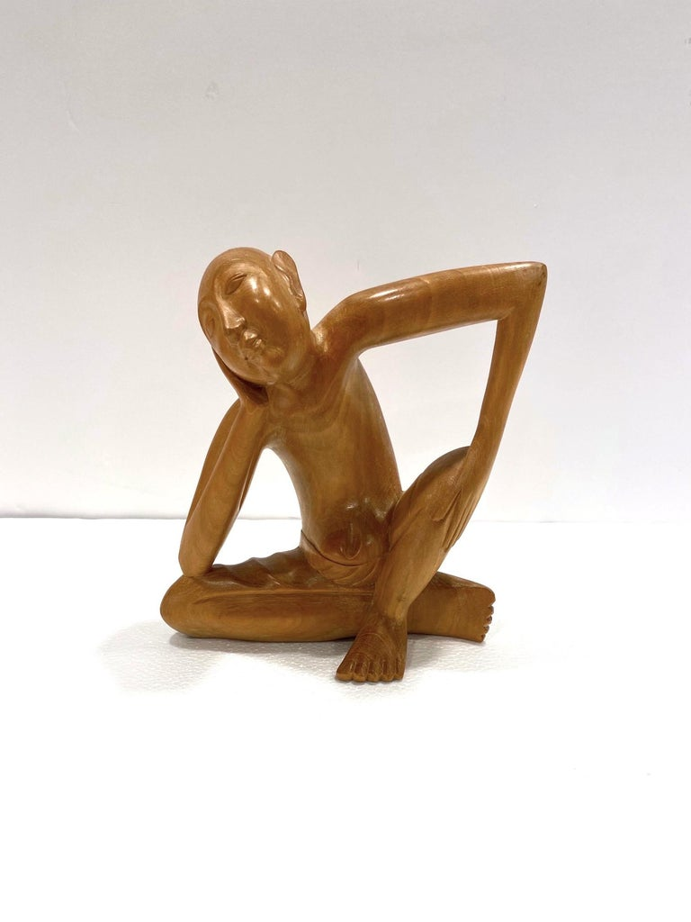 1970's Balinese figural sculpture in solid reclaimed suar wood. Artisan made with exquisite hand carved details. This sculpture features a sitting man in a pensive or contemplative state, perhaps a daydreamer. The striking posture creates a linear