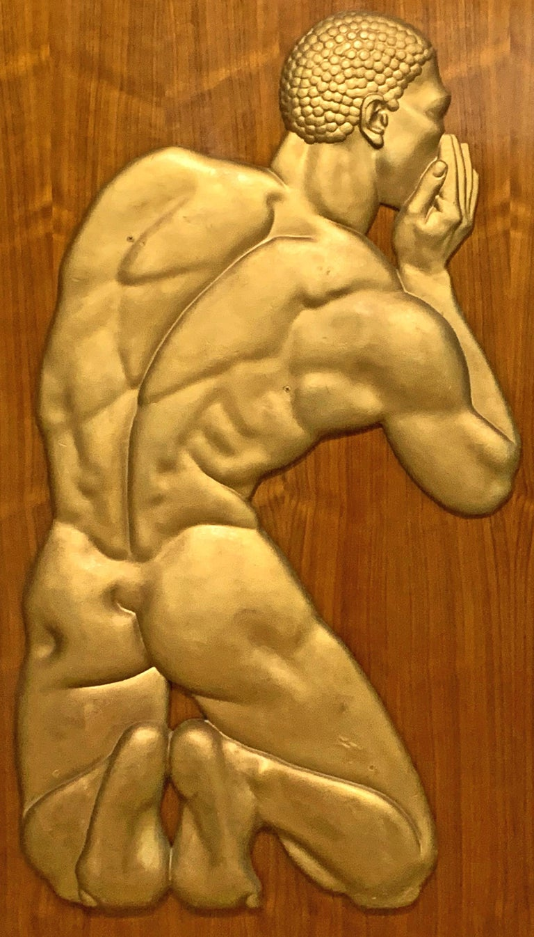 Extremely fine and unique, this large gold-finished plaster bas relief sculpture of a kneeling Black male figure, whispering into the ear of an unseen companion, once graced the lobby of an Art Deco hotel in Florida. The sculptor captured the form