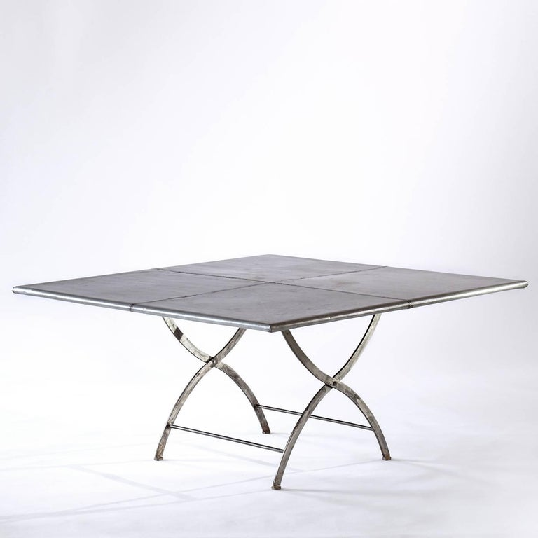 This Industrial-style table has a striking top made of four zinc sheets welded together to form a square cross piece with smooth, rounded edges and a distressed metal finish. The handmade base of steel has a clear varnish and features two rounded