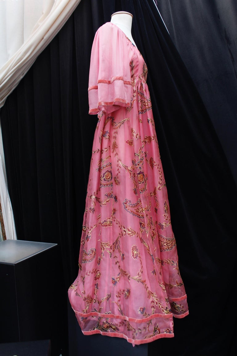 THEA PORTER COUTURE (Made in England) Long dress composed of pink organza painted with floral pattern underlined with golden over stitching. The silk chiffon sleeves are decorated with two velvet stripes matching the bottom of the dress