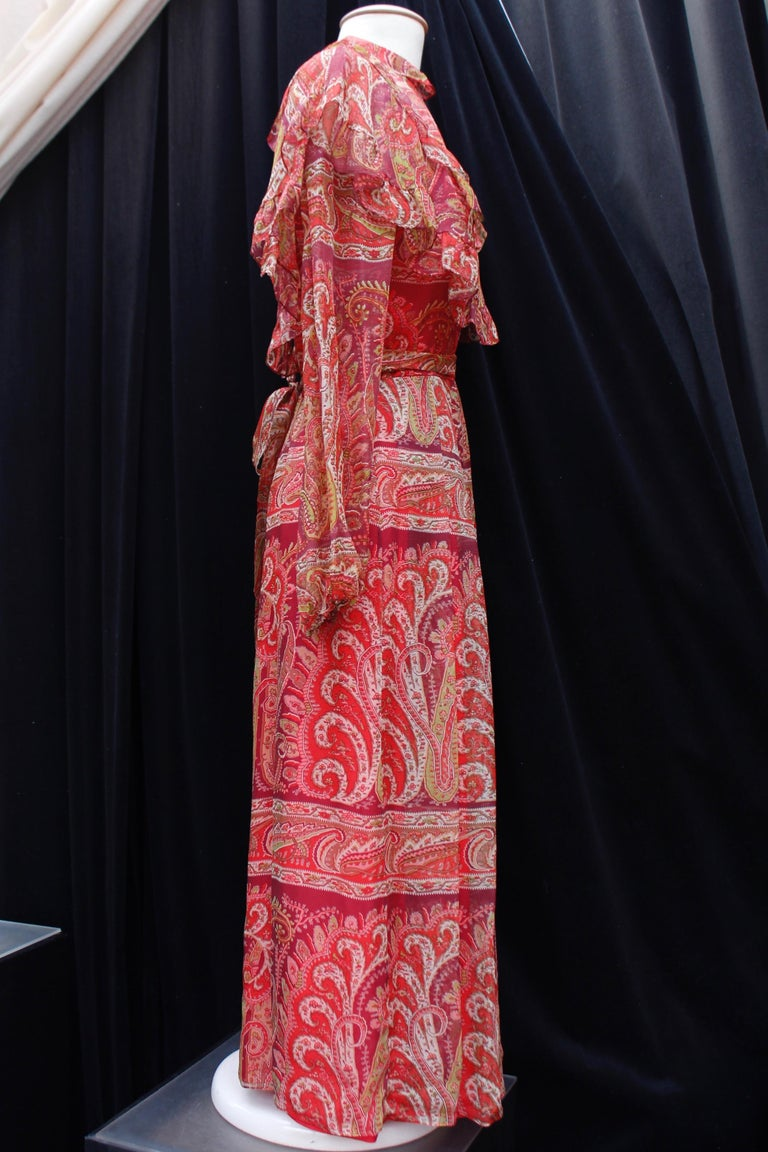 THEA PORTER (Made in France) Beautiful long bohemian style dress composed of silk chiffon printed with a Paisley pattern in red, white and green tones. The long sleeves are tightened at the bottom by elastic. The bust features flounces and the waist
