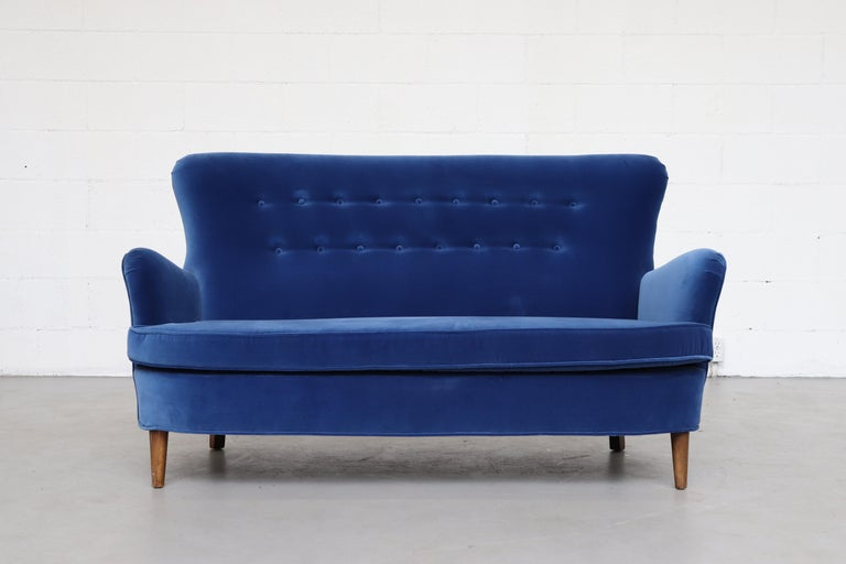 Theo Ruth love seat by Artifort in newly upholstered cobalt blue velvet with tapered legs, in original condition. Finn Juhl Similarity.