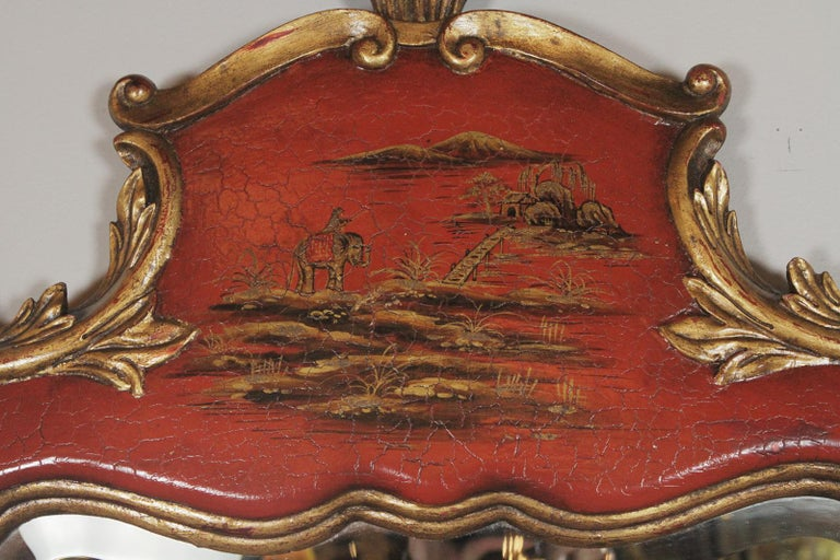Theodore Alexander red lacquer and gilt chinoiserie mirror. Hand painted and lacquered in a rare rechinoiserie finish with bold gilt accents. The frame with an aged crackle finish to give an old world appeal. The mirror is hand beveled.
