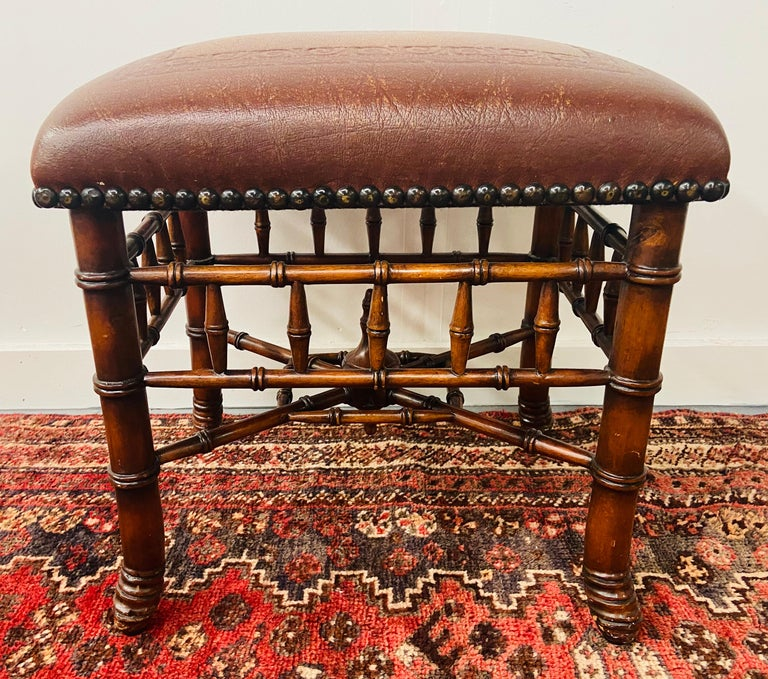 A gorgeous Theodore Alexander hand carved stool or ottoman featuring bamboo base turned legs and wavy