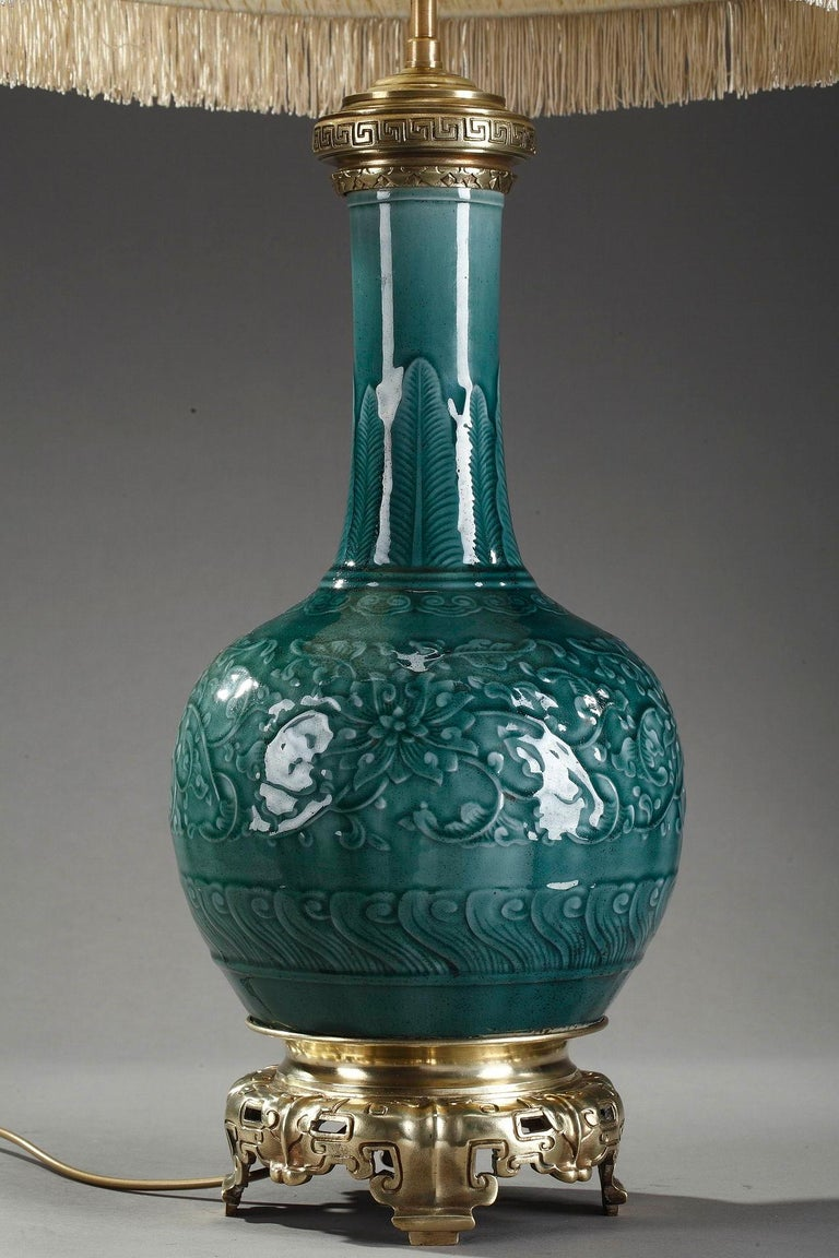 Theodore deck ormolu-mounted green porcelain vase. As in traditional Persian art, the lamp is bottle-shaped, with a wide rounded body leading to a long and slender neck. The table lamp is highlighted in relief under a green glaze with Persian and