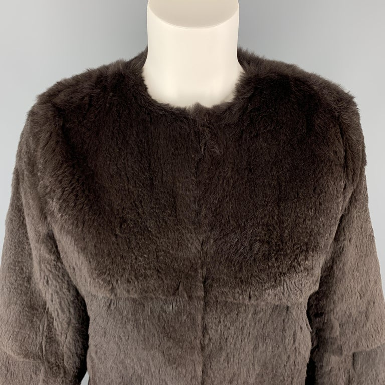 THEORY jacket comes in muted taupe brown rabbit fur with a round, collarless neckline, slit pockets, and hook eye closures.   Excellent Pre-Owned Condition. Marked: S  Measurements:  Shoulder:15 in. Bust: 36 in. Sleeve: 25 in. Length: 21 in.