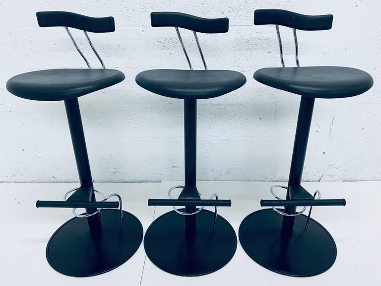 Three bar height Italian Postmodern bar chairs inspired by Memphis Milano. Made of black lacquered steel with black moulded rubber seats and backs.