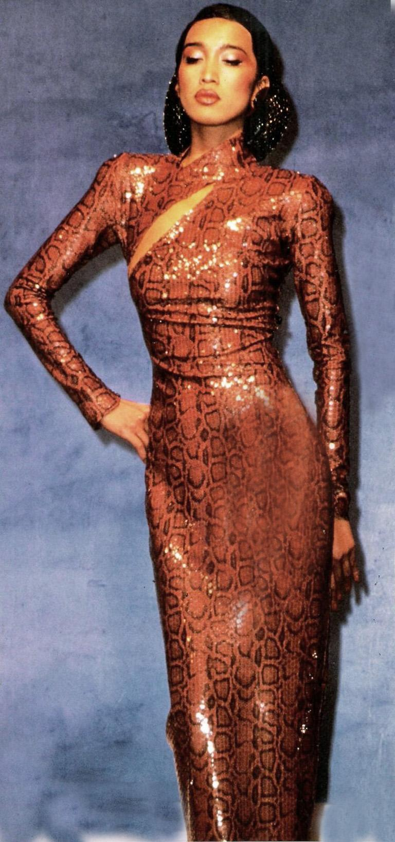 1983 Thierry Mugler body hugging python print evening dress overlaid in clear sequins.   A distinct Mugler silhouette features a high neckline; asymmetrical slit bodice and back kick pleat. Back zipper closure; unlined.   Neckline and wrists