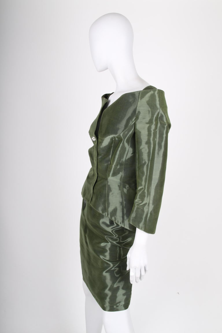 Two-piece suit by Thierry Mugler in olive green shimmery silk. A vintage dream!  The jacket has a wide neckline and front closure with concealed push buttons. Tailored fitting with 7/8 sleeves. Fully lined.  The skirt has a little less than