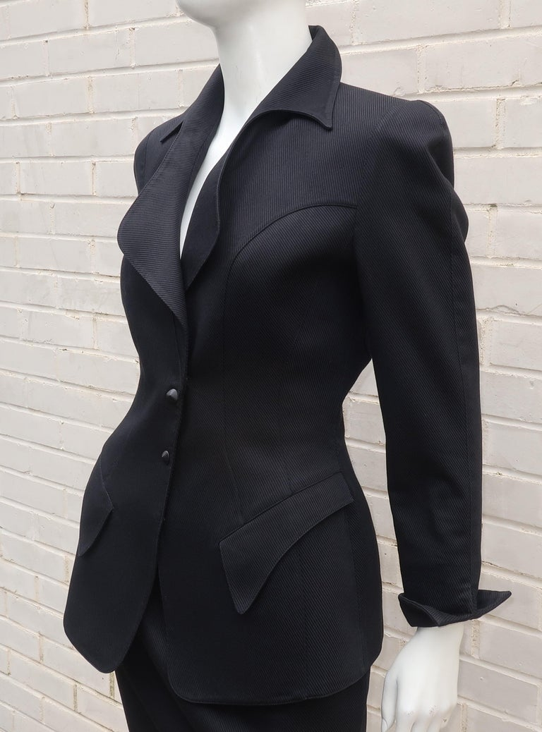Thierry Mugler warm weather weight black cotton skirt suit with a ribbed texture.  The jacket snaps at the front with faux closures and offers Mr. Mugler's iconic sculptural silhouette with a stylized pointy collar, pockets, upturned cuffs and a