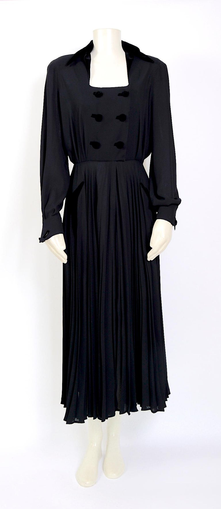 Thierry Mugler couture 1980s vintage black crepe dress with black velvet detailing on the collar, buttons, cuffs, pockets, and an attached full plissé soleil skirt. This dress has been in our collection for some time now and again we are so