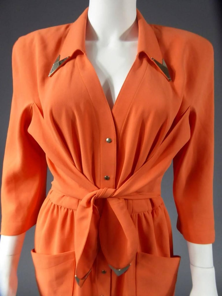 Circa 1988  France  Mid-length orange gown shoulder three quarter sleeves signed Thierry Mugler .Closes on the front with a buttonhole of ten silver snap buttons and a stitched belt on the hips ending with two silver chevrons at the ends recalling
