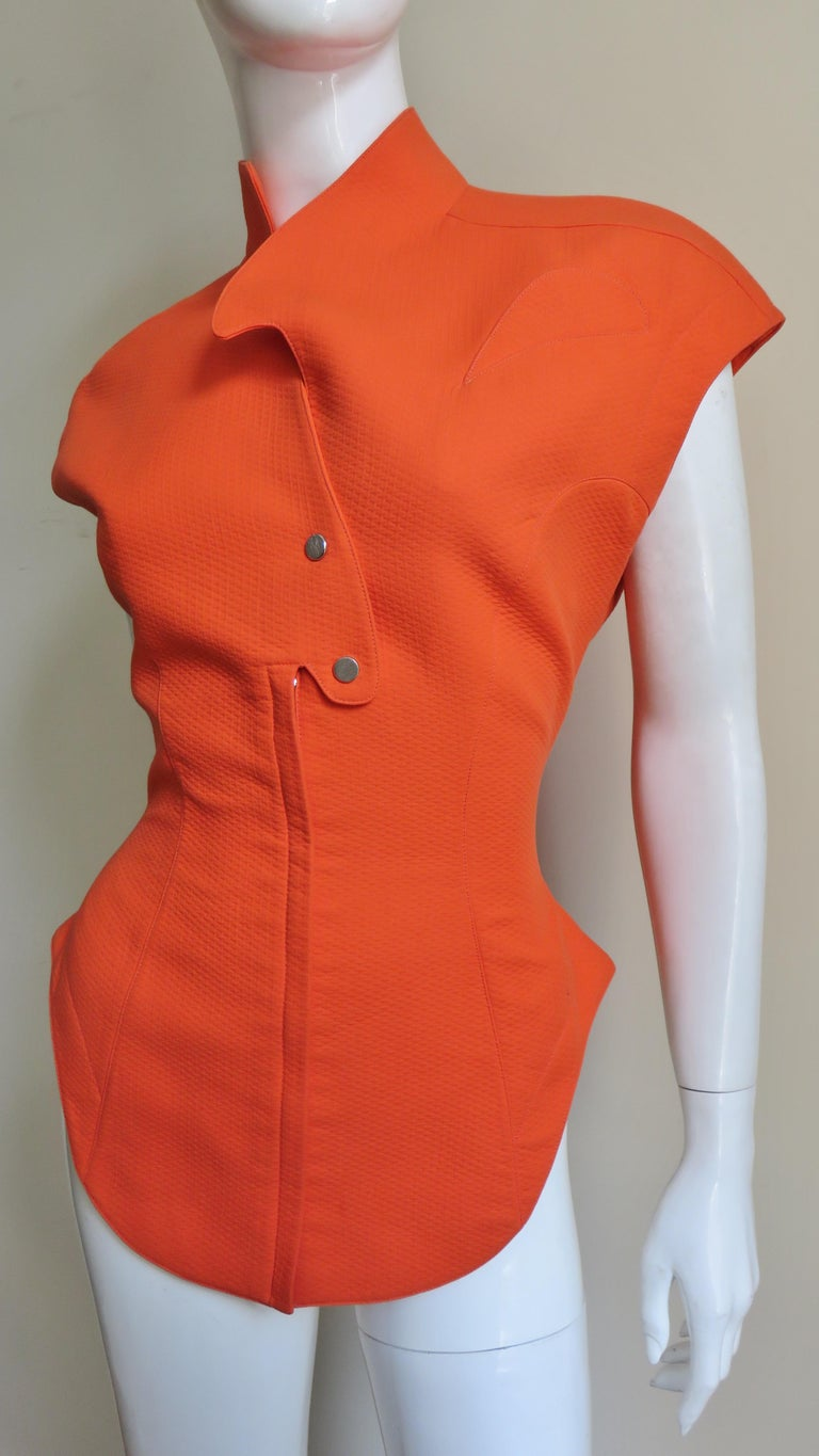 A fabulous jacket, top in orange cotton from Thierry Mugler.  It has extended shoulders forming cap sleeves, a curved stand up collar, shirt tail hem, a small curved chest pocket, and seaming cinching in the waist.  The top is fully lined and closes
