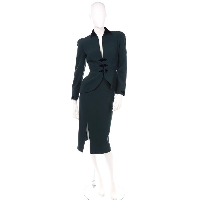 This vintage forest green wool Thierry Mugler 2 piece skirt suit is so spectacular! We love the front opening of the jacket with the double black velvet covered buttons and velvet lined pointed collar. This suit is a signature Mugler shape and