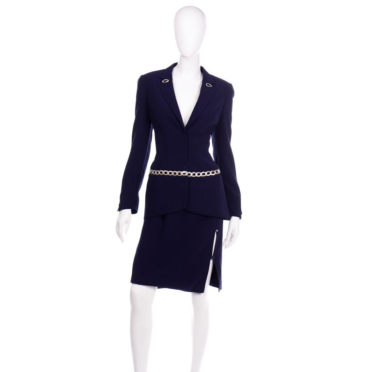 This is such an incredible Thierry Mugler navy skirt suit in with a  matte silver-tone chain link detail. The jacket has fabric covered metal snap buttons in the center front opening and shoulder pads for structure. In classic Thierry Mugler