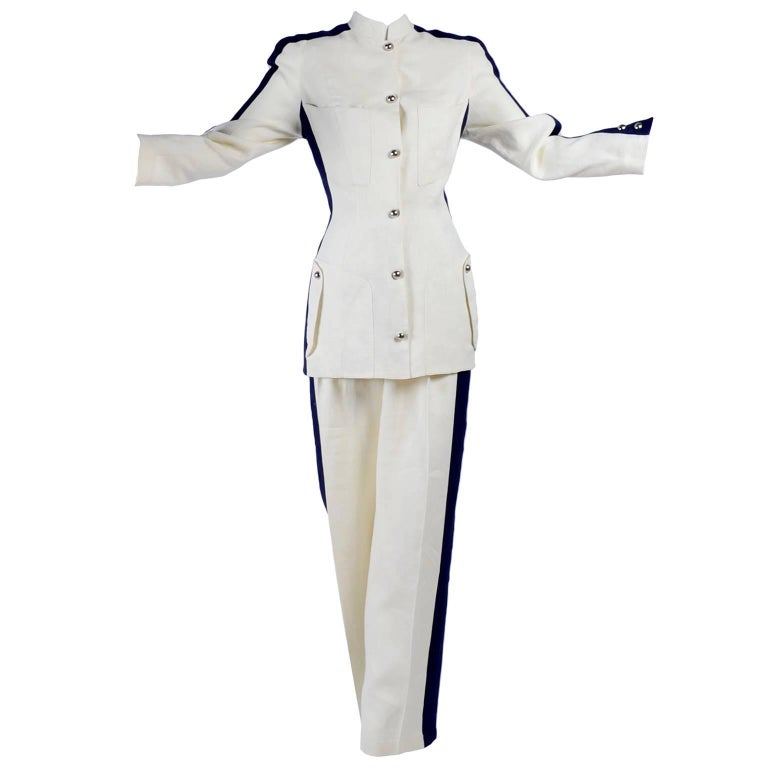This is a fabulous 2 piece linen blend pantsuit designed by Thierry Mugler that includes a pair of high waist trousers and a long jacket.  Both the jacket and pants have wide navy blue stripes up the side.  The jacket is lined with slight shoulder