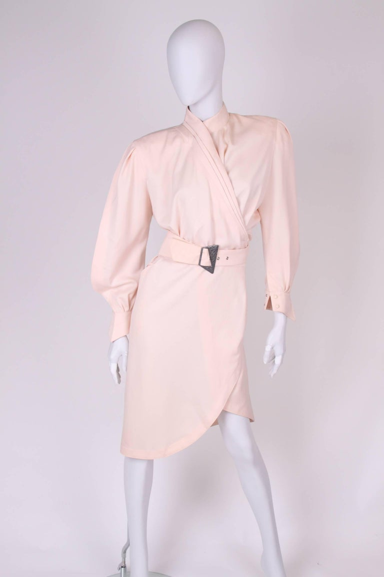 Vintage alert! Straight from the eighties: a salmon pink wrap dress by Thierry Mugler. We love it!  This high necked dress has more than knee length and has a matte silver buckle closure. Two welt pockets on the hips. No lining, large padding in the