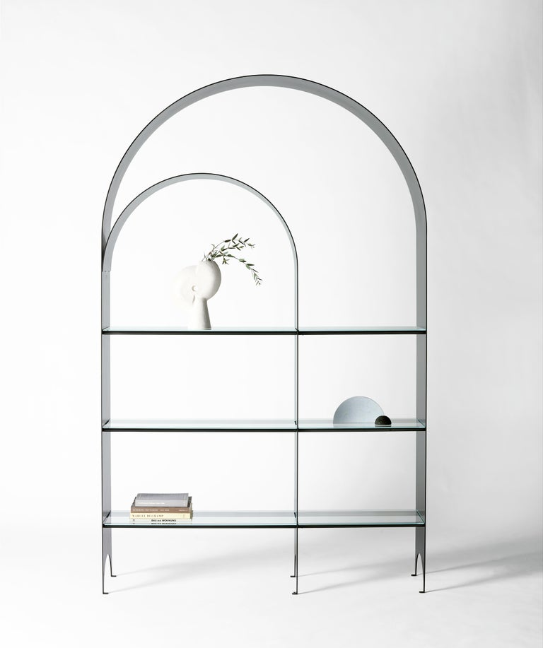 The thin shelf is the newest addition to the thin series, a collection exploring the potential of rigid yet pliant steel plates. The blackened steel arch of the Thin Shelf delicately extends upward from the floor tracing a double line along the