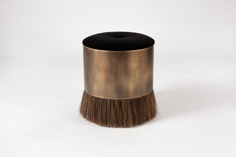 Konekt's signature Thing Stools are available in four different styles. Thing 4 features a luxuriously upholstered top, a brass-plated steel drum and horse hair. Refined yet wild, Thing 4's unique personality is accentuated with a distinctive