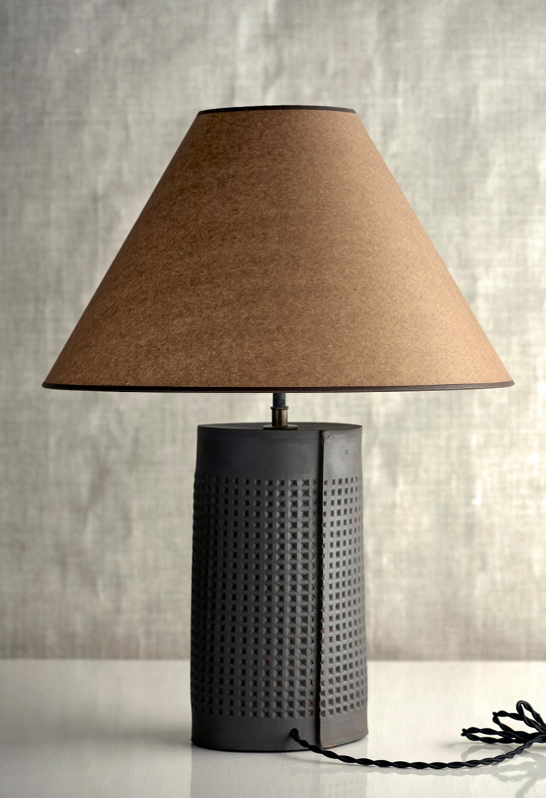 Description  Handmade stoneware slab construction. Lamps are individually crafted and one of a kind.  Finish  Matte black glaze. Antique brass fittings, dimmer switch on socket. Braided black cloth cord and Kraft paper