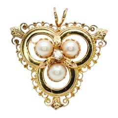 This Antique 14 Karat Yellow Gold Brooch with Pearls and Diamonds in the Center
