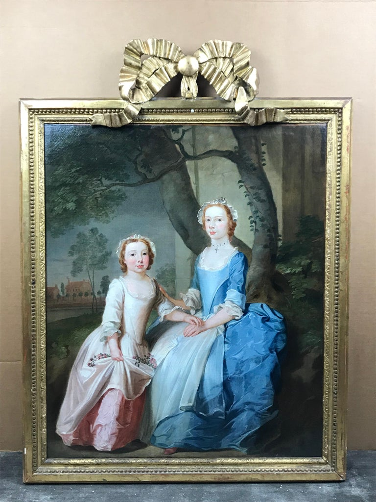 A portrait of two sisters sitting on a wooded bank with a view of a country hous - Painting by Thomas Bardwell