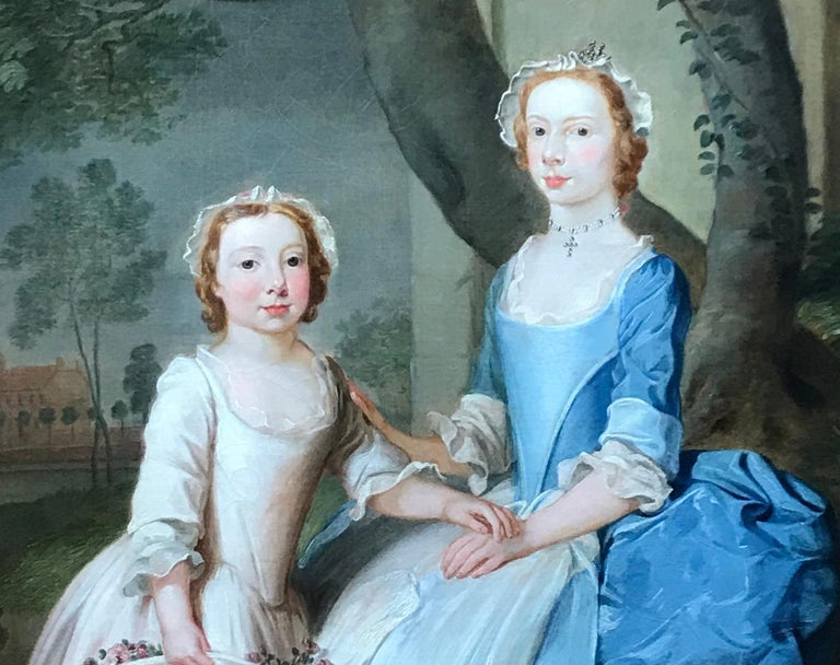 A portrait of two sisters sitting on a wooded bank with a view of a country hous - Old Masters Painting by Thomas Bardwell