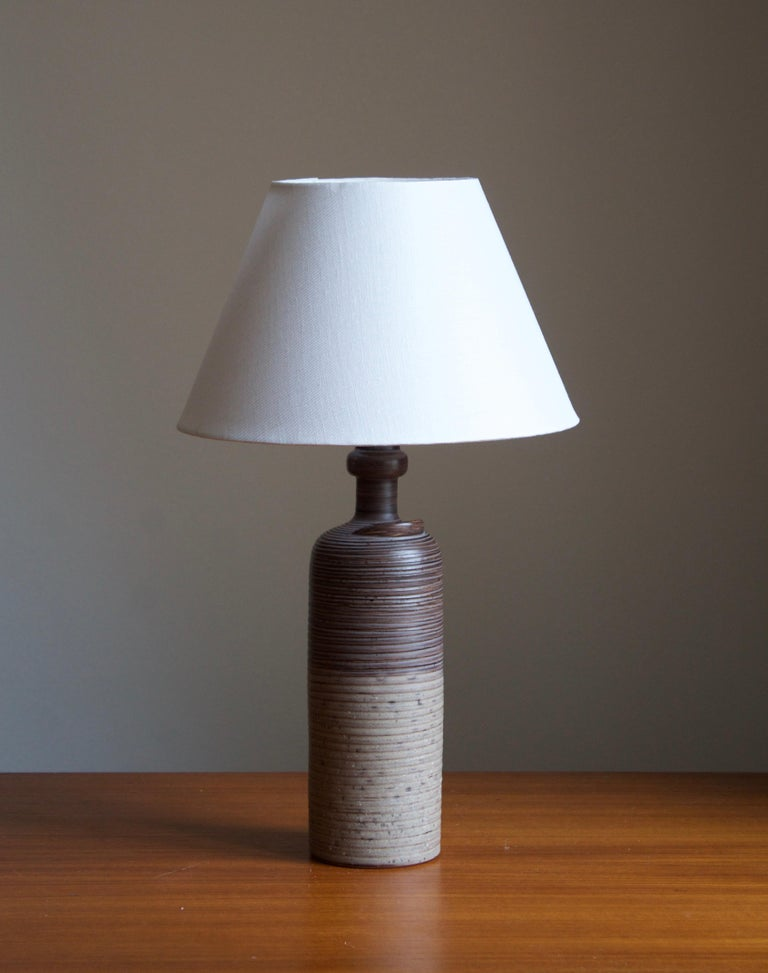 A table lamp designed by Thomas Hellström, produced by Nittsjö, Sweden, c. 1960s.  Features subtle incised decor and a sculptural detail.  Stated dimensions exclude lampshade. Height includes socket. Sold without lampshade.