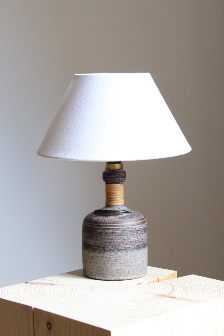 A table lamp designed by Thomas Hellström, produced by Nittsjö, Sweden, c. 1960s.  Features subtle incised decor and a sculptural detail as well as original cane wrapping.  Stated dimensions exclude lampshade. Height includes socket. Sold without