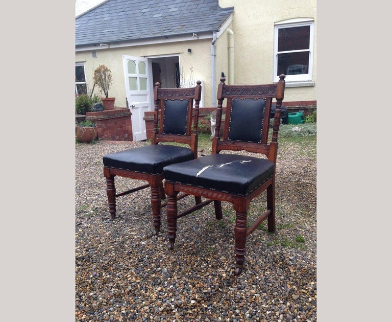 Thomas Jeckyll in the style of. A good quality pair of aesthetic movement dining chairs with sunflower carved details to the backs, subtle details below the seats with ring turned legs and original ceramic and brass castors.