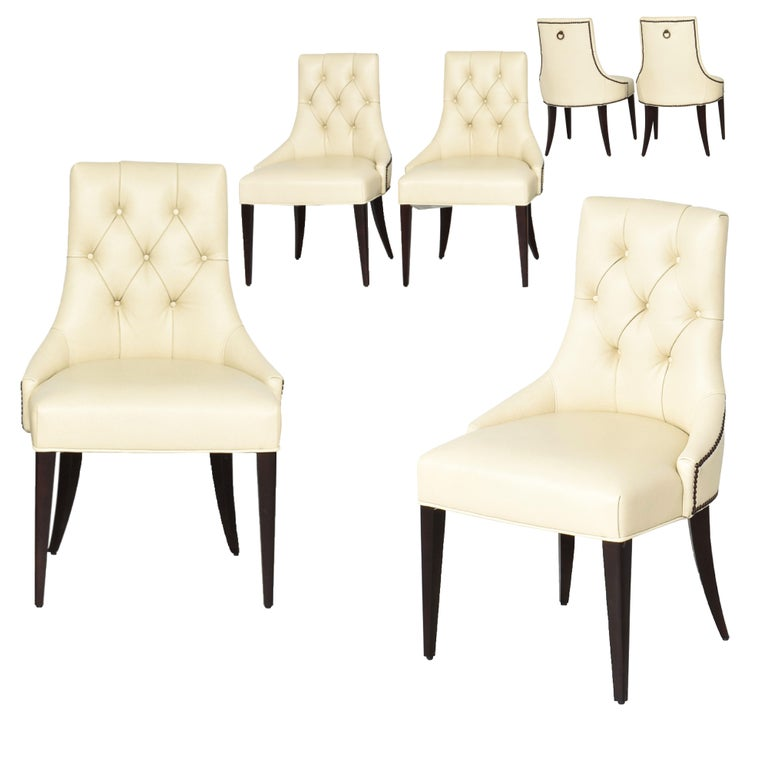 Thomas Pheasant for Baker Furniture Company Tufted cream ritz dining chair, No. BA7841. Mink base. Six available. I believe the bases are mink finish, LL1190 ivory semi-aniline leather, antique brass/bronze nailhead trim.