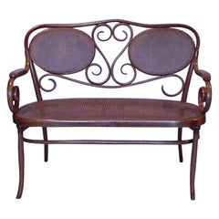 Thonet, A Bentwood Settee with Scrollwork Decoration with a Caned Seat & Back