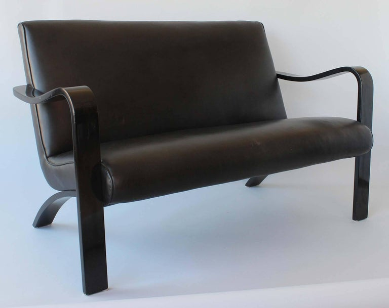 A midcentury bentwood sofa or love seat finished in black lacquer, with faux leather upholstery by Thonet.