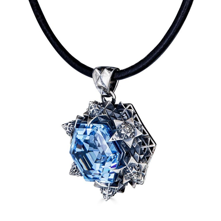 This unique Thoscene Aquamarine Silver Peace Pendant Necklace features an aquamarine stone set in sterling silver. All of the pieces, including this pendant necklace, in John Brevard's Thoscene collection are 3D-printed using cutting edge
