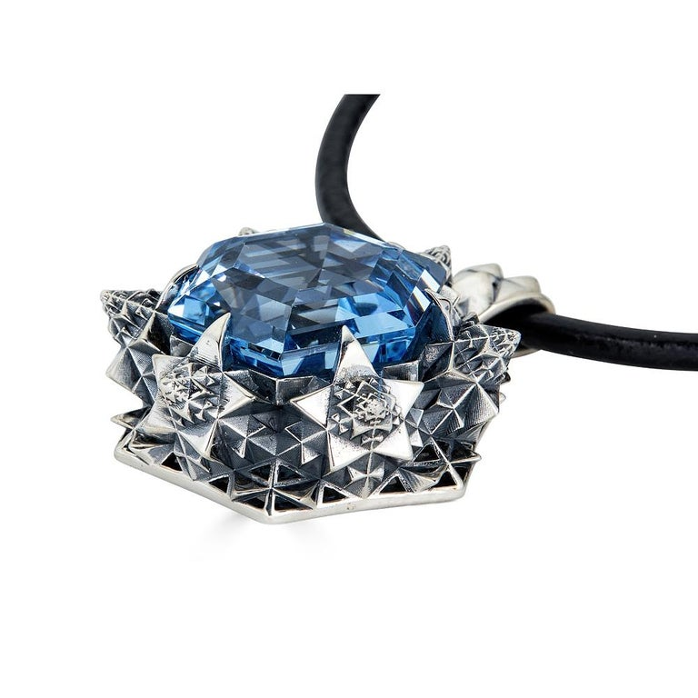 This unique Thoscene Topaz Silver Peace Pendant Necklace features an aquamarine stone set in sterling silver. All of the pieces, including this pendant necklace, in John Brevard's Thoscene collection are 3D-printed using cutting edge technology. The