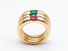 Three 18 Karat Gold Bangles Rings Set with an Emerald, a Sapphire, and a Ruby