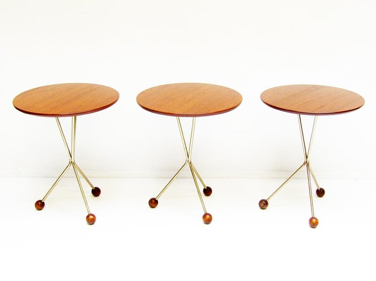 A trio of circular 1950s side tables in teak by Albert Larsson for Alberts Tibro.  Perfect examples of Swedish design, they have atomic brass legs with wooden globe feet.  Carefully restored, they are in excellent structural and aesthetic