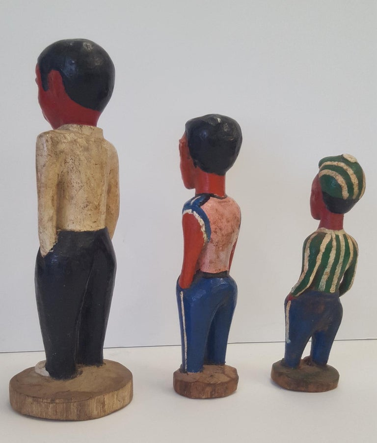 Three ivory coast colonial, hand carved and painted, wooden figures of young fellows. They are painted in various types of casual street dress, and each is differentiated in height and width, and costume.