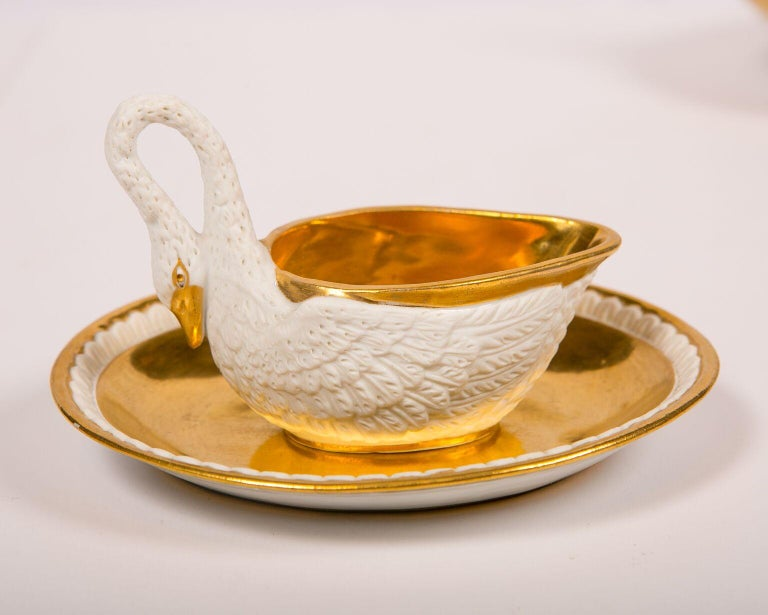 A set of three white and gold porcelain swans made originally as sauce boats each richly gilded (the gilt is in perfect mirror-like condition). The golden sauce boat interior and underplate contrast beautifully with the pure white bisque porcelain