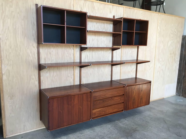 Walnut with metal trim three bay hanging wall unit. fully adjustable. With two doored cabinets and one drawer section and assorted shelves Made by Barzilay.