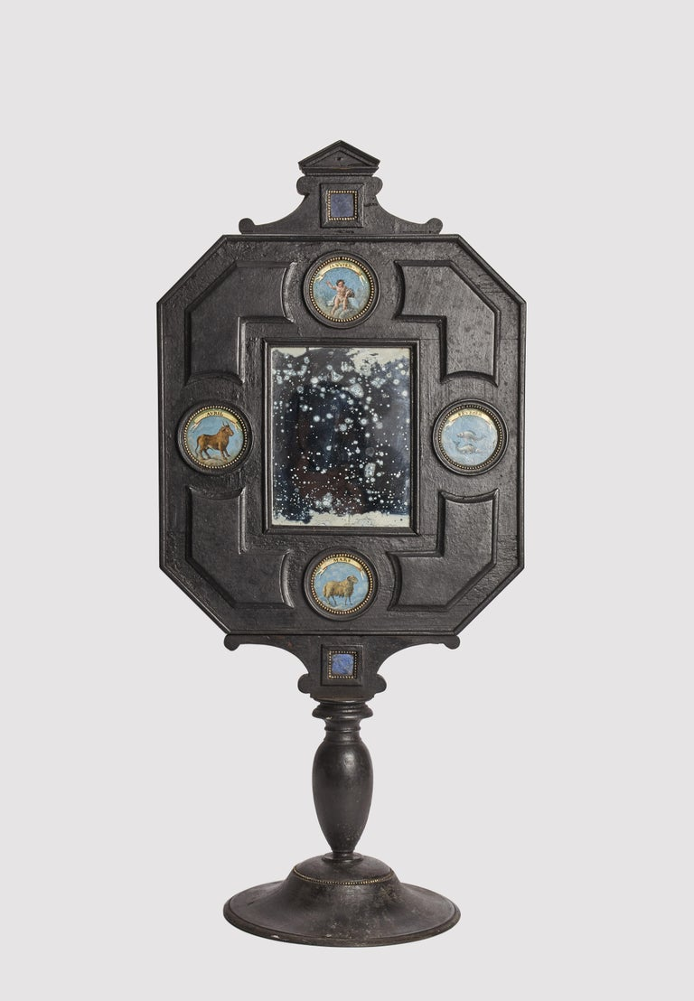 A Wunderkammer three big mirrors with a black octagonal wooden frame, with 2 lapis lazuli embedded in a frame, mounted over a black round wooden base. Each mirror contains 4 round inserts depicting different zodiac signs, painted oil on leather,