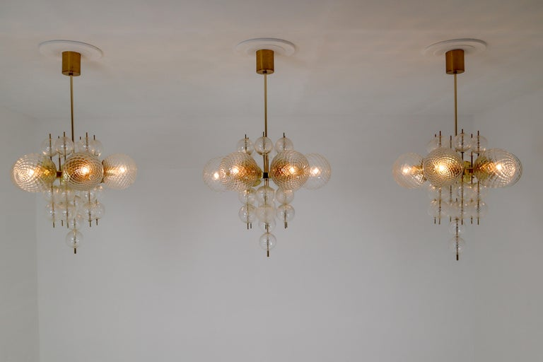 This set of three brass chandeliers was produced by Fa. Preciosa in Kamenicky Senov, Czechoslovakia in the 1970s. A spirited and chic design set of three chandeliers with brass fixture and art-glass. The chandelier with brass frame consist of six