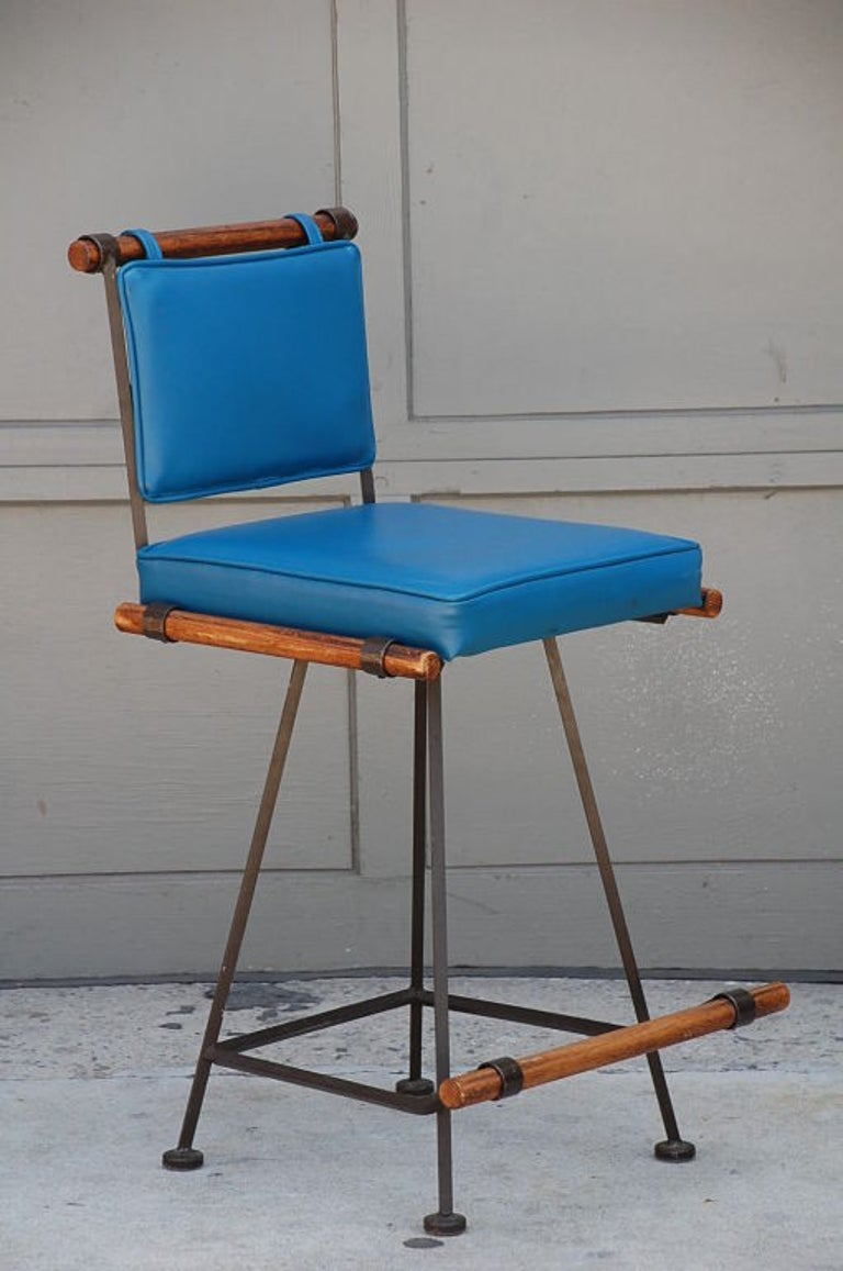 Rare set of 3 original wrought iron and oak swiveling counter stools by Cleo Baldon.  Ideal for comfortable counter height seating (25 in. seat height).  Original blue vinyl upholstery in good condition that can be replaced with C. O. M. (1 yard