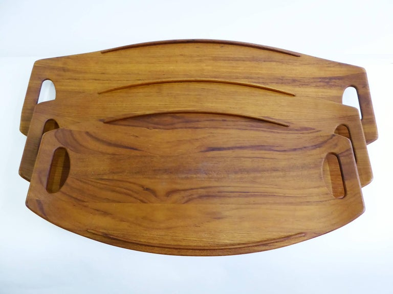 Three classic Fjord Teak Trays, designed in 1956 by Jens Quistgaard for Dansk Designs. All made in Denmark, with early Four Ducks Dansk logo and the larger two stamped also with 802 and 803. The 801, 802, and 803 teak trays which originally date